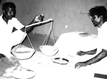 Food as offering (India, 1963). Members of the church who don't have money to give offer a handful of rice, wheat, or corn. Here, Evangelist Manohar Khakha and a lay member are weighing the grain. The grain will be sold and the money put into the church fund. Source: Mennonite Church USA Archives
